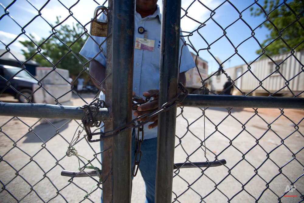 In this Aug. 3, 2015 photo, a Dominican Republic border agent locks a gate that separates the D.R. town of Pedernales from the Haitian town of Anse-a-Pitres. According to the government, more than 288,000 people applied for residency in the D.R. and so far, about 25,000 have received their documents to stay and work, and another 40,000 have been approved. Authorities also say 66,000 people have returned to Haiti since the June 17 deadline to apply for legal residency. (AP Photo/Dieu Nalio Chery)