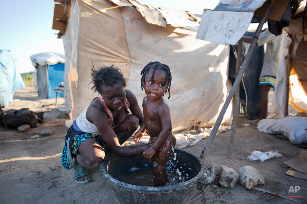In this Aug. 3, 2015 photo, Haitian Molene Charles bathes her 15-month-old son Geralson next to their makeshift home in Anse-a-Pitres, Haiti, on the border with the Dominican Republic, after fleeing the D.R. by foot due to threats from locals. Hundreds of thousands of people applied for residency in the D.R., but many could not qualify for residency because they could not meet the requirements. Others say they have also felt increasing hostility toward people from Haiti in the Dominican Republic. (AP Photo/Dieu Nalio Chery)