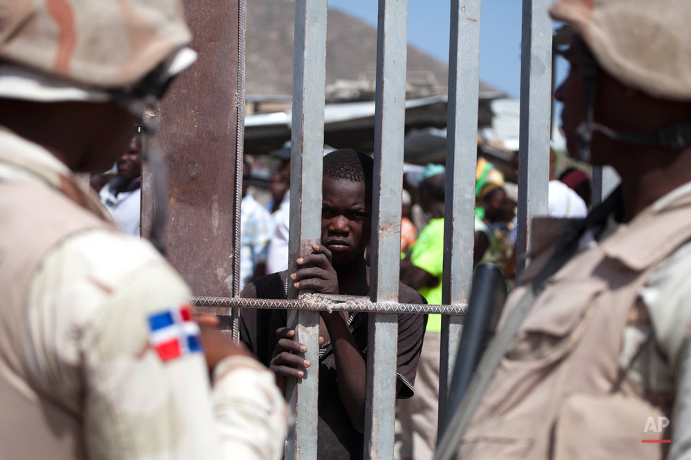 In this Aug. 4, 2015 photo, a Haitian youth peers from behind a border fence separating the Haitian town of Malpasse and the Dominican Republic town of Jimani. Thousands of Haitians and people of Haitian descent have fled the D.R. in recent weeks, setting up encampments along the Haiti side of the border, cut off from the jobs that sustained them in the D.R. (AP Photo/Dieu Nalio Chery)