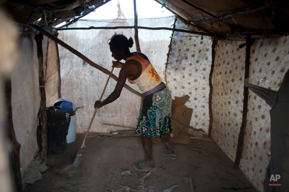 In this Aug. 3, 2015 photo, Haitian Molene Charles sweeps the dirt floor of her family's makeshift home in Anse-a-Pitres, Haiti, on the border with the Dominican Republic. Molene, 28, who lived and worked in the D.R. for 14 years as a street vendor, fled her home with her husband Elissene Jean Louis and their four children after receiving threats from locals. (AP Photo/Dieu Nalio Chery)