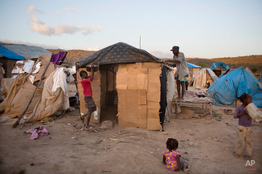 In this Aug. 3, 2015 photo, Haitian Elissene Jean Louis patches up his family's makeshift home in Anse-a-Pitres, Haiti, on the border with the Dominican Republic as his children watch. From left are Edez, 13, 15-month-old Geralson, center, and Celine, 5. Jean Louis, a 61-year-old field worker who fled the D.R. with his family after years of threats from locals, arrived here in May after living and working in the D.R. for four decades. On May 17, his family of six traveled by foot for an entire day to reach the border, leaving their belongings behind. When he returned to check on their home, he found it burned down. (AP Photo/Dieu Nalio Chery)