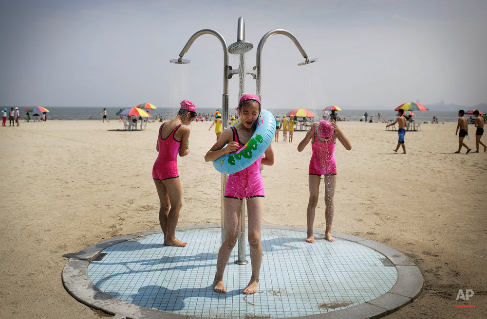 North Korean girls in similar bathing suits stand under a shower at the Songdowon International Children's Camp, Tuesday, July 29, 2014, in Wonsan, North Korea. The camp, which has been operating for nearly 30 years, was originally intended mainly to deepen relations with friendly countries in the Communist or non-aligned world. But officials say they are willing to accept youth from anywhere - even the United States.  (AP Photo/Wong Maye-E)