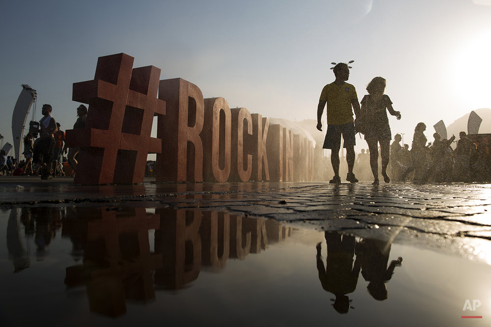 A couple walks past a Rock in Rio sign during the Rock in Rio music festival in Rio de Janeiro, Brazil, Saturday, Sept. 19, 2015. (AP Photo/Felipe Dana)
