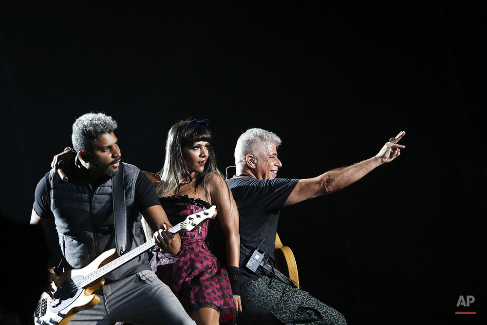 Brazilian singer Lulu Santos, right, performs with Andrea Negreiros, center, and Jorge Ailton during his show at the Rock in Rio music festival in Rio de Janeiro, Brazil, Saturday, Sept. 26, 2015. (AP Photo/Felipe Dana)
