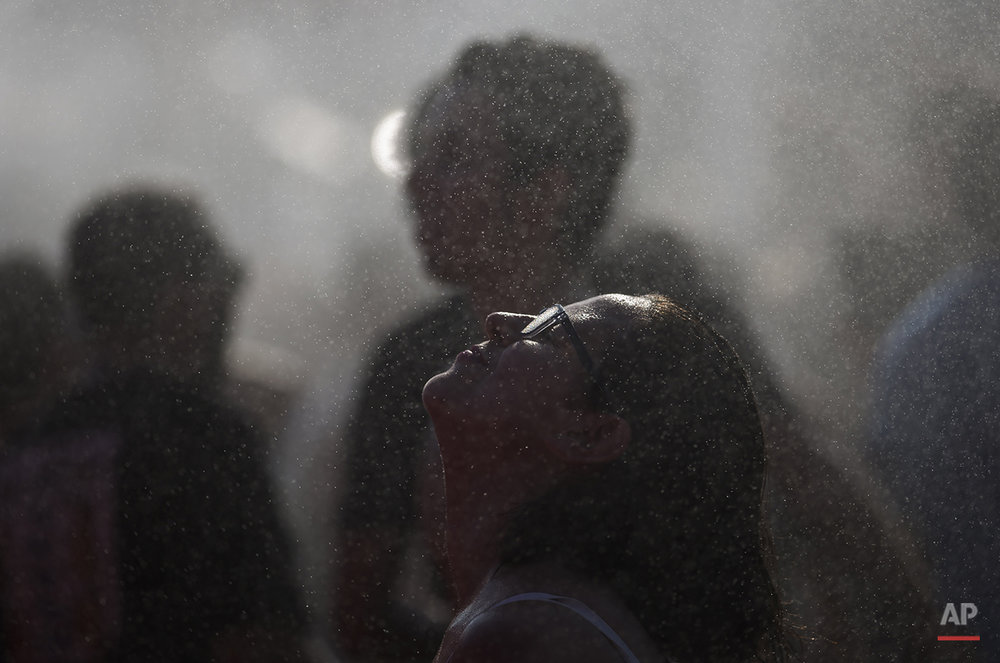 A woman cools off from the heat during the Rock in Rio music festival in Rio de Janeiro, Brazil, Thursday, Sept. 24, 2015. (AP Photo/Leo Correa)