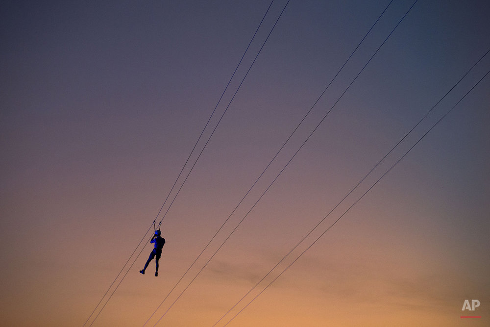 A music fan slides down a zip-line at the Rock in Rio music festival in Rio de Janeiro, Brazil, Friday, Sept. 18, 2015. Thousands are expected to turn out for the music festival that is marking 30 years since the first Rock in Rio. Grammy-winning legend Elton John and American heavy-metal band Metallica are among those invited to perform. (AP Photo/Felipe Dana)
