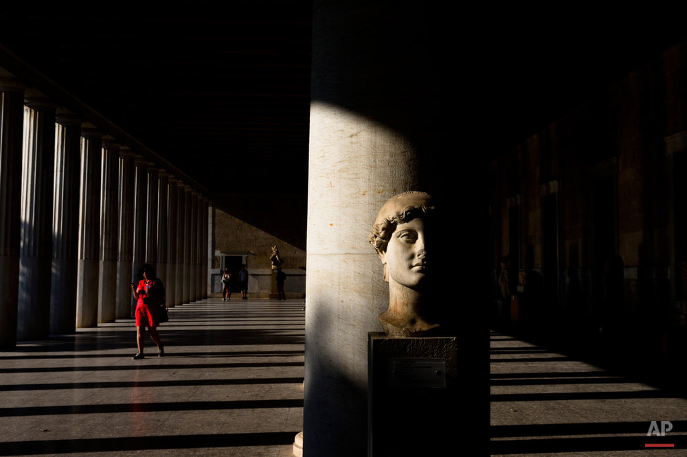 A woman walks behind a 2nd century A.D. marble head of victory inside Stoa of Attalos, at ancient agora, in Athens, Sunday, Aug. 30, 2015.  (AP Photo/Petros Giannakouris)