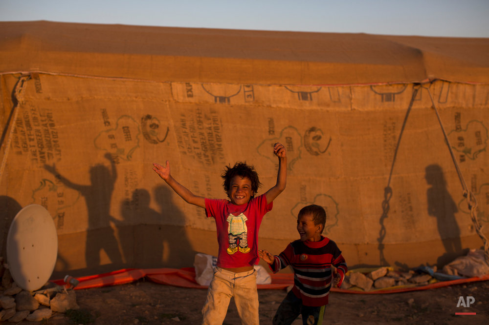 Syrian refugee children react in front of the camera while playing at an informal tented settlement near the Syrian border on the outskirts of Mafraq, Jordan, Tuesday, Aug. 25, 2015. (AP Photo/Muhammed Muheisen)