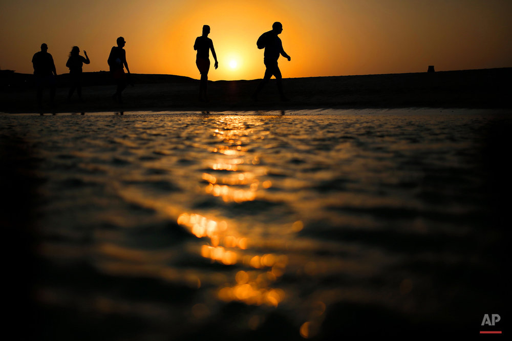 In this picture taken Thursday, Aug. 20, 2015, tourists walk on the Giftun Island beach as the sun sets over the Red Sea in Hurghada, Egypt. (AP Photo/Hassan Ammar)