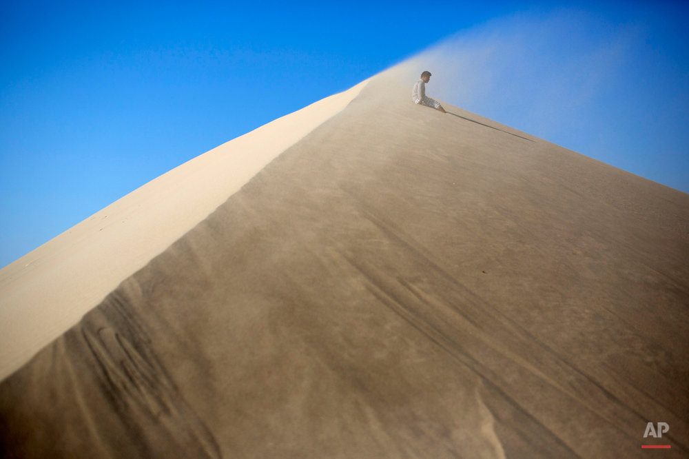 Luis Enrique Tuanama, 17, rests while climbing the Cerro de Saraja , a mountain of sand, in Ica, Peru, Friday, Aug. 7, 2015. (AP Photo/Rodrigo Abd)