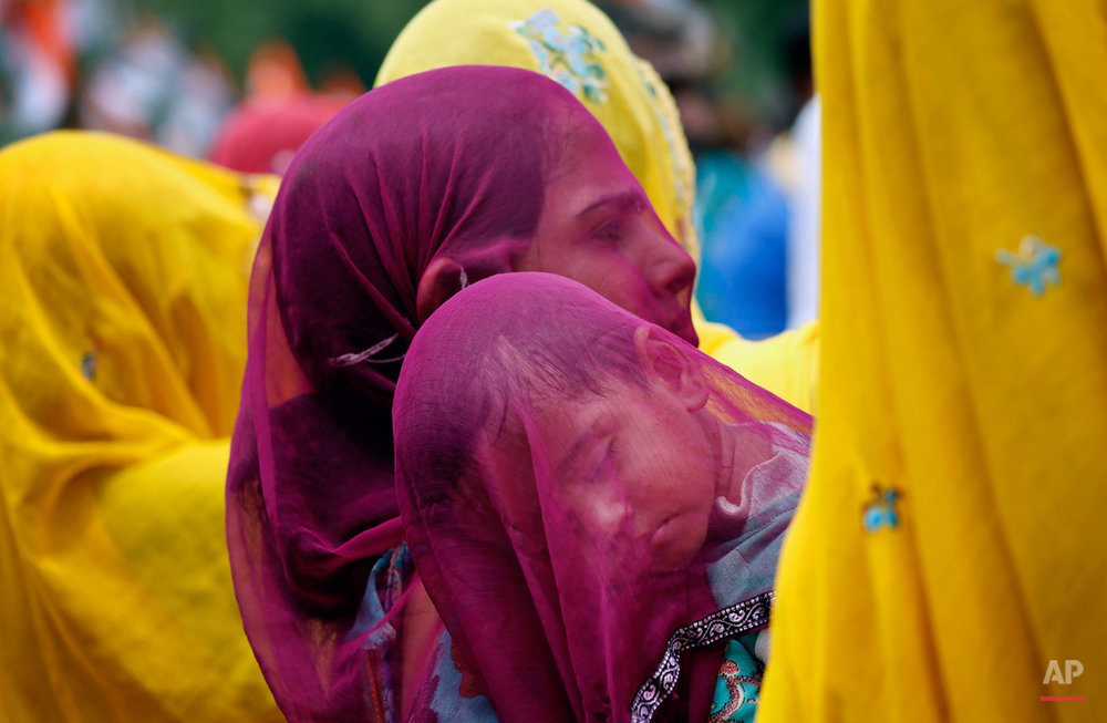 An Indian village woman covers a sleeping child with her veil as she carries him on her shoulder at Ajmer in Indiaís Rajasthan state, Wednesday, Aug. 5, 2015. Married Hindu women in parts of Indian states observe a veil, or cover their heads as a long followed tradition. (AP Photo/Deepak Sharma)