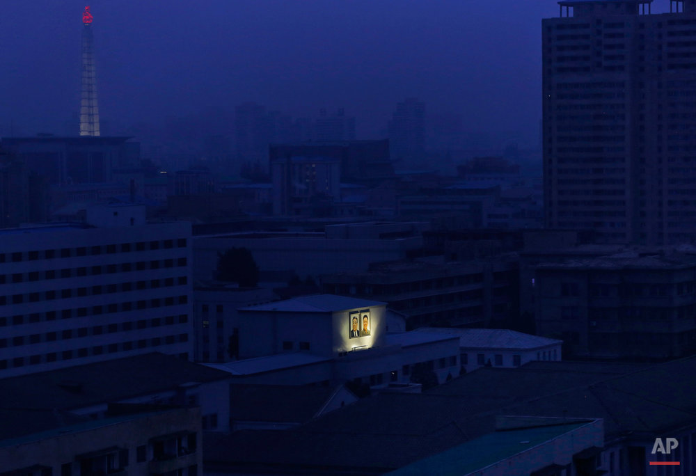 Portaits of the late North Korean leaders Kim Il Sung, left, and Kim Jong Il glow on the facade of a building as the Juche Tower, top left, one of the city's landmarks, is seen in the background at dawn in Pyongyang, North Korea, Wednesday, Aug. 19, 2015. (AP Photo/Dita Alangkara)