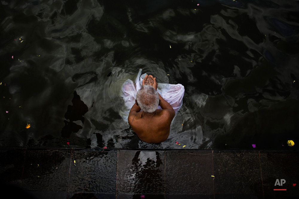 In this Wednesday, Aug. 26, 2015, file photo, a Hindu devotee performs a holy dip in the Godavari River during Kumbh Mela, or Pitcher Festival, in Nasik, India. Millions of Hindus are expected to immerse themselves in the Godavari River as a way to cleanse themselves of sin and come closer to God at this year's Kumbh Mela festival. (AP Photo/Bernat Armangue, File)