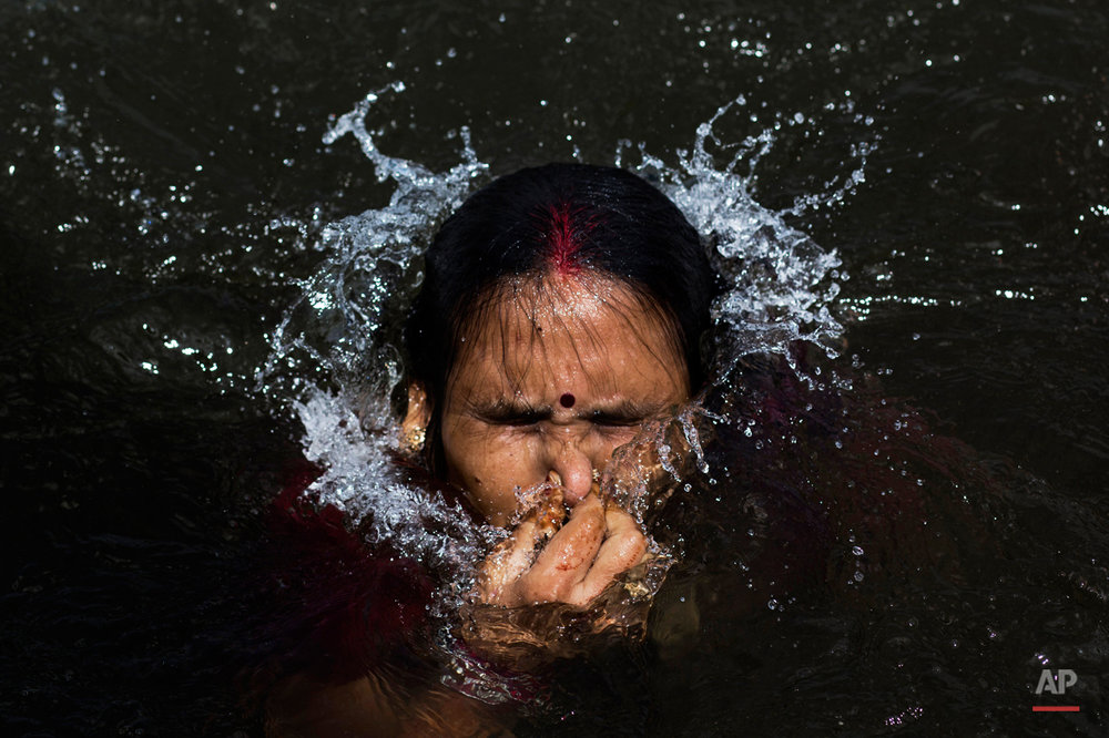 In this Wednesday, Aug. 26, 2015 photo, a Hindu devotee performs a holy dip in the Godavari River during Kumbh Mela, or Pitcher Festival, in Nasik, India. Millions of Hindus are expected to immerse themselves in the Godavari River as a way to cleanse themselves of sin and come closer to God at this year's Kumbh Mela festival. (AP Photo/Bernat Armangue)