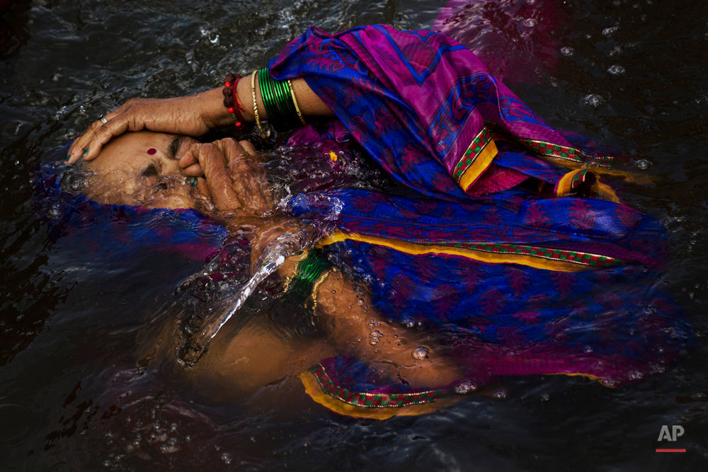 In this Wednesday, Aug. 26, 2015, photo, a Hindu devotee performs a holy dip in the Godavari River during Kumbh Mela, or Pitcher Festival, in Nasik, India. Millions of Hindus are expected to immerse themselves in the Godavari River as a way to cleanse themselves of sin and come closer to God at this year's Kumbh Mela festival. (AP Photo/Bernat Armangue)