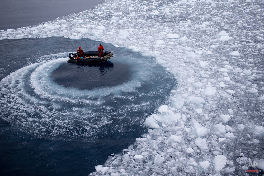 In this Jan. 22, 2015 photo, Chilean Navy officers push away ice by moving their boat in circles as they approach the Aquiles navy ship where they will pick up international scientists and take them to Chile's scientific Station Bernardo O'Higgins in Antarctica. While tourists come to Antarctica for its beauty and remoteness, scientists are all business. What they find could affect the lives of people thousands of miles away. (AP Photo/Natacha Pisarenko)