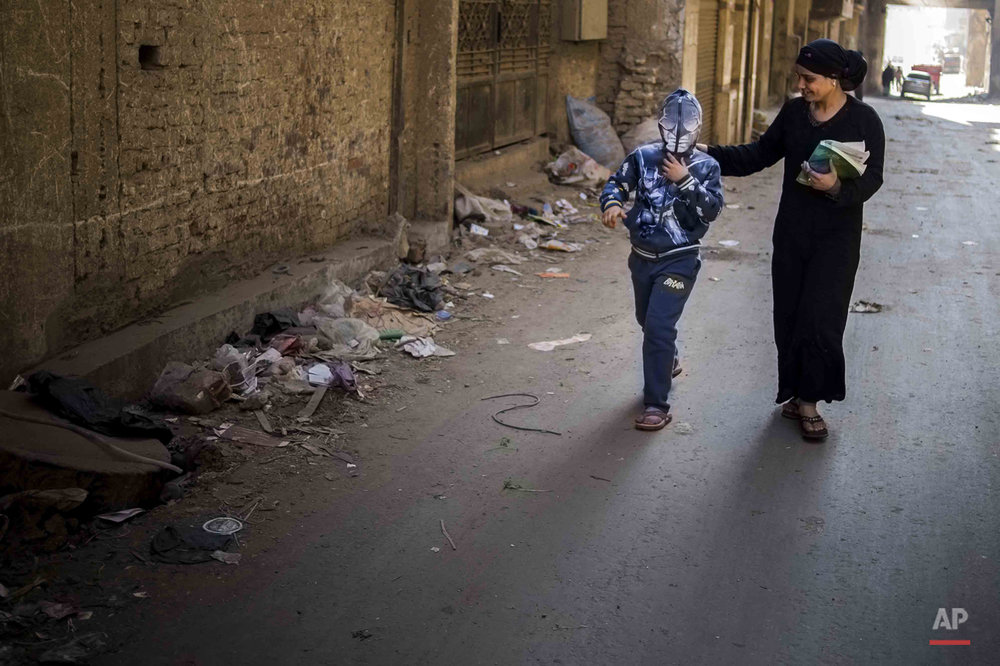 In this picture taken on Feb. 8, 2015, 10-year-old Abanoub Samaan Nazmy and his mother Haniya Magdy Khila walk to school in the Manshiet Nasr neighborhood of Cairo, Egypt. Coptic Christian Abanoub lost his father to suspected military snipers as he protested in March 2011 over the burning of a church. (AP Photo/Hamada Elrasam)