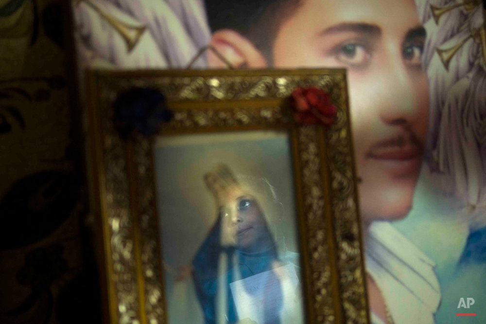 In this picture taken pn Feb. 2, 2015, 9-year-old Youstina Malak Rasmy, who lost her father to suspected military snipers as he protested in March 2011 over the burning of a church, looks at a portrait of him that hangs in her home in the Manshiet Nasr neighborhood of Cairo, Egypt. For Youstina, art helps deal with her grief. ìIíd like to be a painter like him, because I love his paintings and to meet him in heaven,î she says. (AP Photo/Hamada Elrasam)
