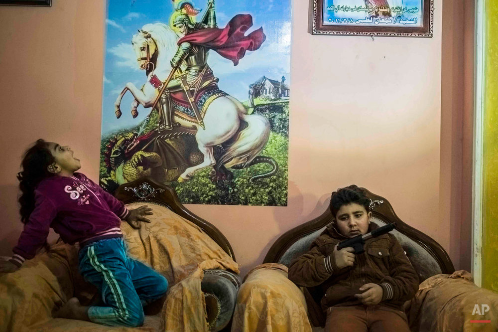 In this picture taken on Feb. 2, 2015, 10-year-old Abanoub Samaan Nazmy, right, holds a toy gun as he plays with his sister in the living room of their home in the Manshiet Nasr neighborhood of Cairo, Egypt. Abanoub, who is a Coptic Christian, lost his father to suspected military snipers as he protested in March 2011 over the burning of a church. In Egypt, the years of turmoil following its 2011 uprising have seen revolutionary graffiti fade away as the country slowly tries to move on, but hidden scars remain for children who grew up during the chaos and lost loved ones.(AP Photo/Hamada Elrasam)