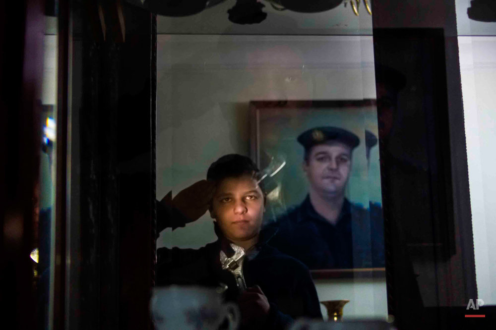"In this picture taken on Jan. 30, 2015, 13-year-old Adham Ehab Anwar, whose policeman father was shot to death in an attack on his station after the bloody security force breakup of Islamist sit-ins in Cairo in 2013, salutes as he looks at himself in the mirror at his home in Giza, Egypt. For Adham, joining the military brings solace. Holding a wrench before a portrait of his late father, Adham says he wants to invent ""anti-terrorism"" devices. A portrait of his late father hangs on the wall. (AP Photo/Hamada Elrasam)"