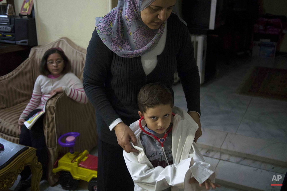 In this picture taken on Feb. 1, 2015, 4-year-old Mohammed Hesham, whose police officer father was killed last year after chasing suspected terrorists, plays doctor at his home, in Cairo, Egypt. In Egypt, the years of turmoil following its 2011 uprising have seen revolutionary graffiti fade away as the country slowly tries to move on, but hidden scars remain for children who grew up during the chaos and lost loved ones. (AP Photo/Hamada Elrasam)