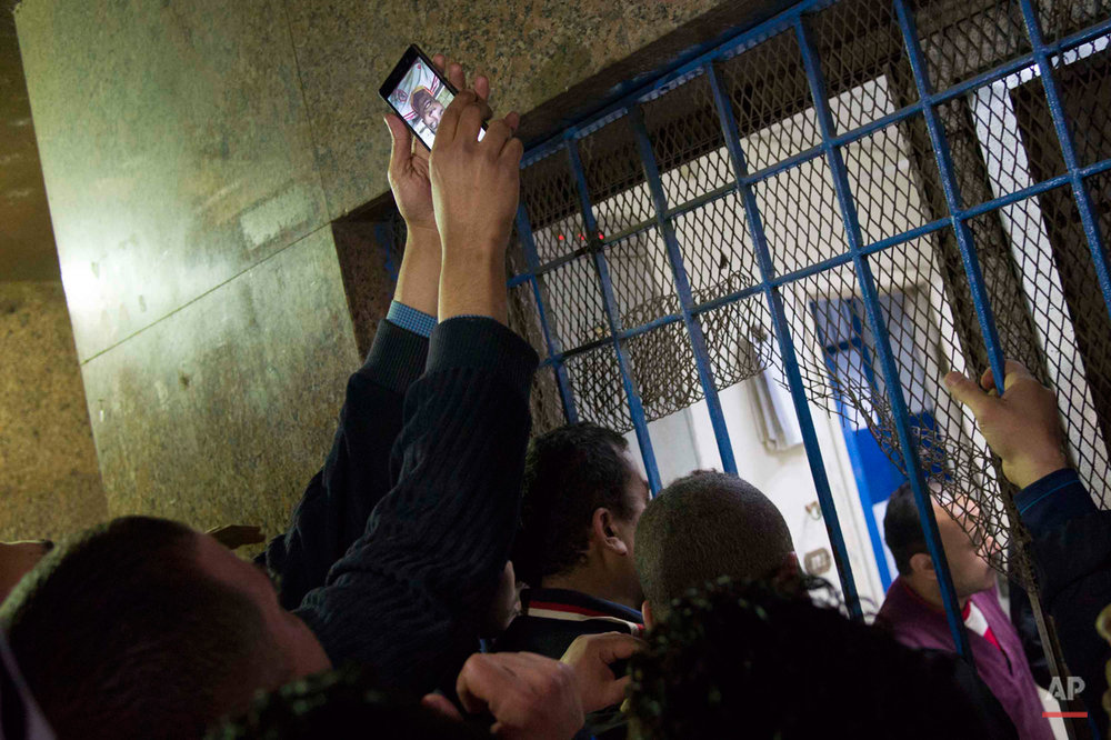 In this picture taken on Feb. 8, 2015, family and friends of soccer fans killed in a stadium riot wait outside Zeinhom morgue in Cairo, Egypt. The years of turmoil following Egypt's 2011 uprising have seen revolutionary graffiti fade away as the country slowly tries to move on, but hidden scars remain for children and youth who grew up during the chaos and lost loved ones. (AP Photo/Hamada Elrasam)