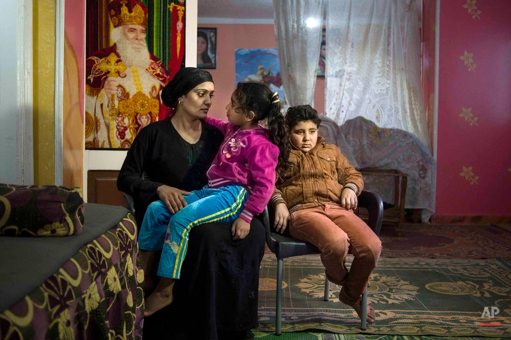 In this picture taken on Feb. 2, 2015, 10-year-old Abanoub Samaan Nazmy, right, rests at his home with his mother and younger sister, in the living room of their home in the Manshiet Nasr neighborhood of Cairo, Egypt. Abanoub, who is a Coptic Christian, lost his father to suspected military snipers as he protested in March 2011 over the burning of a church. Grief touches children of all kinds in this country, cutting across Christian and Muslim families, the sons of the outlawed Muslim Brotherhood group to the daughters of police officers and soldiers. (AP Photo/Hamada Elrasam)