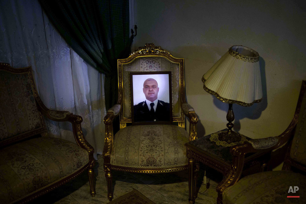 This picture taken on Jan. 30, 2015 shows a portrait of the slain father of Adham Ehab Anwar, who was shot to death in an attack on his station after the bloody security force breakup of Islamist sit-ins in Cairo in 2013, on the chair he used to sit on at his home in Giza, Egypt. For 13-year-old Adham, the idea of joining the military brings solace. Holding a wrench before a portrait of his late father, Adham says he wants to invent ìanti-terrorism devices.î  (AP Photo/Hamada Elrasam)