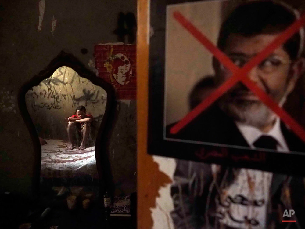 "In this picture taken on Sept. 26, 2015, Egyptian activist Tarek Tito sits in the room he shared with his brother in Cairo, Egypt. Tarek has been accused of two crimes: being associated with the Muslim Brotherhood and taking part in the burning of the Muslim Brotherhood's headquarters. His younger brother Mahmoud has been detained for more than 200 days for wearing a t-shirt that says, ""a homeland without torture."" (AP Photo/Hamada Elrasam)"