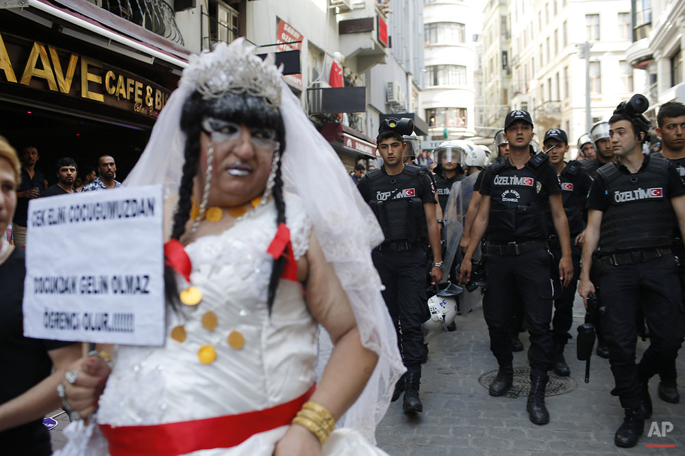 Turkish police walk as they push back participants of a gay pride event in Istanbul, Sunday, June 28, 2015. Turkish police used water cannons and tear gas to clear gay pride demonstrators from Istanbul's central square. It wasn't immediately clear why the police intervened to push the peaceful if noisy protest away from the area. Demonstrators regrouped a few blocks down the street and continued to dance and chant slogans against homophobia without any further clashes. (AP Photo/Emrah Gurel)