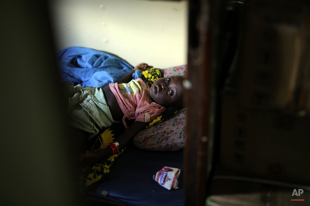A young refugee who fled Burundi's violence and political tension makes the journey on Lake Tanganyika, Tanzania from Kagunga to the port city of Kigoma in a ship freighted by the UN, Saturday May 23, 2015. An outbreak of cholera has infected 3,000 people in a Tanzanian border region where refugees fleeing political unrest in Burundi have massed, the U.N. Refugee Agency said Friday, May 22, 2015. Some 300 to 400 new cases of cholera are being reported daily. At least 31 people — 29 refugees and two Tanzanians — already have died of the disease, according to UNHCR. More than 64,000 Burundians have fled to Tanzania in recent weeks, UNHCR said, escaping the unrest sparked by their president's bid for a third term that many say is unconstitutional. (AP Photo/Jerome Delay)