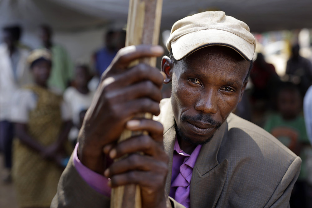 A refugee who fled Burundi's violence and political tension waits to board a ship freighted by the UN, at Kagunga on Lake Tanganyika, Tanzania, Saturday, May 23, 2015 to be taken to the port city of Kigoma. An outbreak of cholera has infected 3,000 people in a Tanzanian border region where refugees fleeing political unrest in Burundi have massed, the U.N. Refugee Agency said Friday, May 22, 2015. Some 300 to 400 new cases of cholera are being reported daily. At least 31 people — 29 refugees and two Tanzanians — already have died of the disease, according to UNHCR. More than 64,000 Burundians have fled to Tanzania in recent weeks, UNHCR said, escaping the unrest sparked by their president's bid for a third term that many say is unconstitutional. (AP Photo/Jerome Delay)