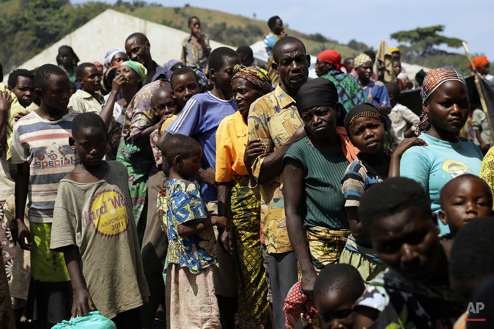 Refugees who fled Burundi's violence and political tension wait to board a ship freighted by the UN, at Kagunga on Lake Tanganyika, Tanzania, Saturday, May 23, 2015 to be taken to the port city of Kigoma. An outbreak of cholera has infected 3,000 people in a Tanzanian border region where refugees fleeing political unrest in Burundi have massed, the U.N. Refugee Agency said Friday, May 22, 2015. Some 300 to 400 new cases of cholera are being reported daily. At least 31 people — 29 refugees and two Tanzanians — already have died of the disease, according to UNHCR. More than 64,000 Burundians have fled to Tanzania in recent weeks, UNHCR said, escaping the unrest sparked by their president's bid for a third term that many say is unconstitutional. (AP Photo/Jerome Delay)