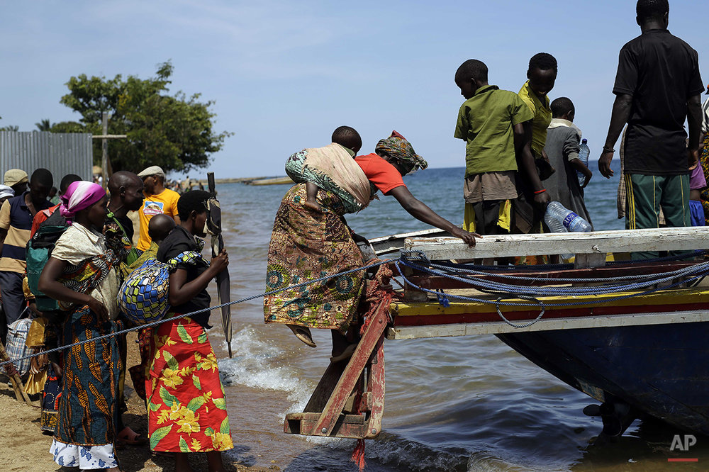 Refugees who fled Burundi's violence and political tension board a speedboat to reach  a ship freighted by the UN, at Kagunga on Lake Tanganyika, Tanzania, Saturday, May 23, 2015 to be taken to the port city of Kigoma. An outbreak of cholera has infected 3,000 people in a Tanzanian border region where refugees fleeing political unrest in Burundi have massed, the U.N. Refugee Agency said Friday, May 22, 2015. Some 300 to 400 new cases of cholera are being reported daily. At least 31 people — 29 refugees and two Tanzanians — already have died of the disease, according to UNHCR. More than 64,000 Burundians have fled to Tanzania in recent weeks, UNHCR said, escaping the unrest sparked by their president's bid for a third term that many say is unconstitutional. (AP Photo/Jerome Delay)