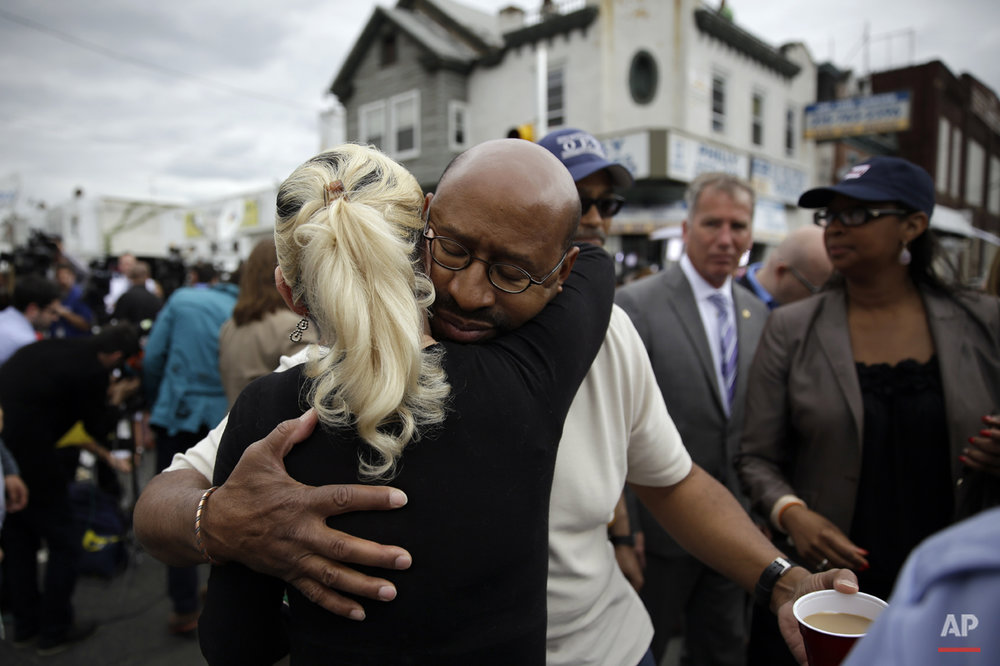 Philadelphia Mayor Michael Nutter, center right, hugs Lori Dee Patterson, a nearby resident, after she handed him a cup of coffee after he spoke at a news conference near the scene of a deadly Amtrak train derailment, Wednesday, May 13, 2015, in Philadelphia. (AP Photo/Matt Slocum)
