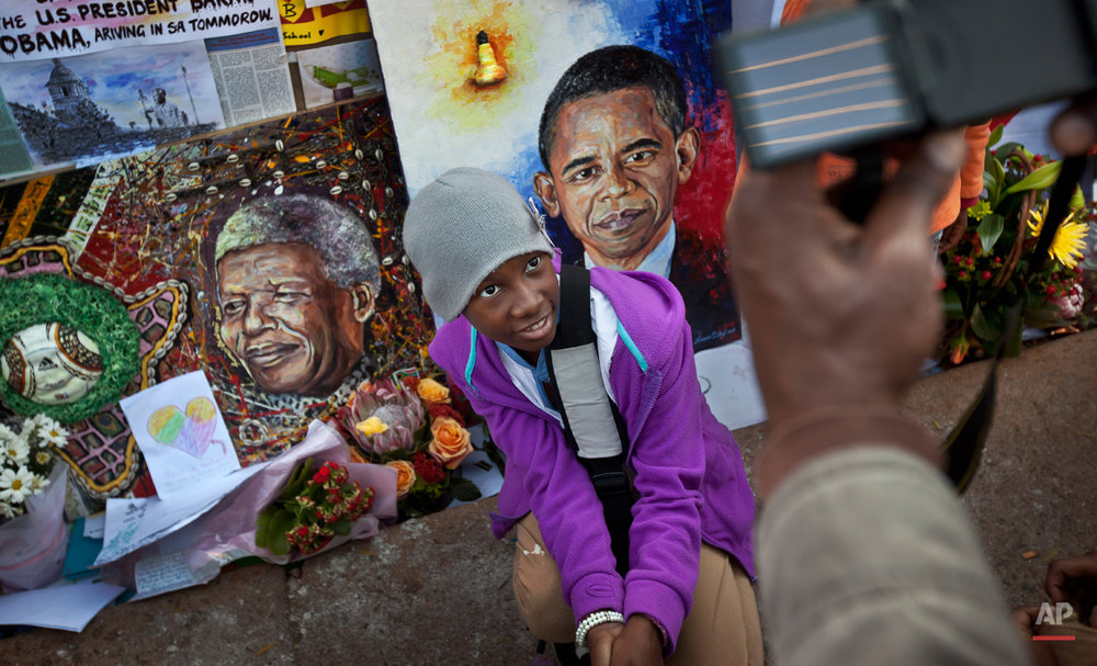 In this Saturday June 29, 2013 photo, children squat to have their photograph taken by their parents next to paintings of President Barack Obama, center, and former South African President Nelson Mandela, left, outside the Mediclinic Heart Hospital where Nelson Mandela is being treated in Pretoria, South Africa. Barack Obama, the United Statesí first African-American president, has captured the imagination of people across the continent where his face shows up on billboards, backpacks, T-shirts and restaurants. On Friday, July 24, 2015 Obama will be visiting Kenya, where his father was born, for a summit on entrepreneurship before heading to Ethiopia to address leaders at the African Union headquarters. Wherever he goes, large crowds are expected to gather and cheer him. (AP Photo/Ben Curtis)