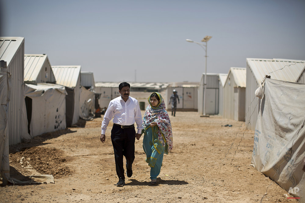 "Nobel Peace Prize laureate Malala Yousafzai, 18, left, and her father Ziauddin hold hands while walking in Azraq refugee camp, Jordan, Monday, July 13, 2015. Rich countries should spend less on weapons in the Syria conflict and more on education, Malala said Monday, calling world leaders ""quite stingy"" as she visited the camp for Syrian war refugees. (AP Photo/Muhammed Muheisen)"