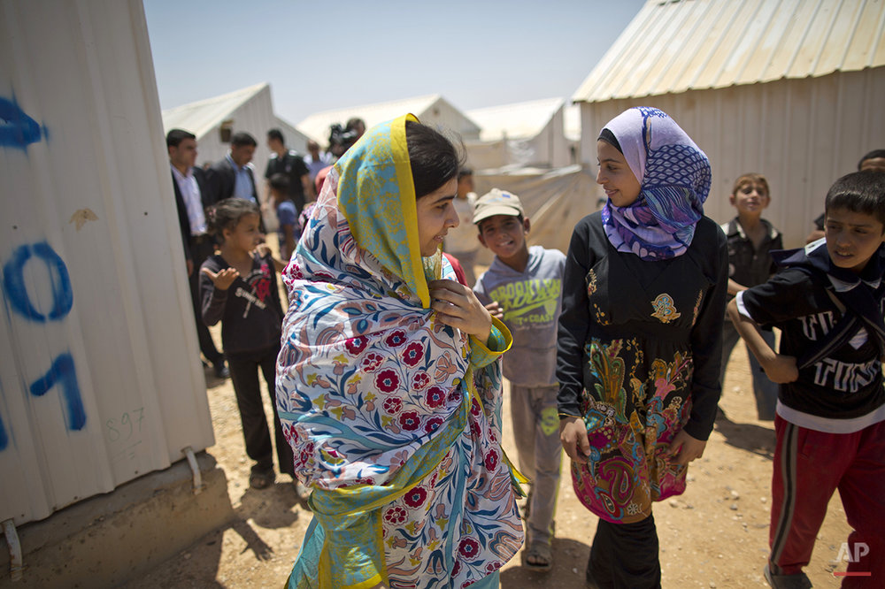 "Nobel Peace Prize laureate Malala Yousafzai, 18, left, walks with Mezon al-Melihan, a 17-year-old refugee from the southern Syrian town of Deraa, during Malala's visit to Azraq refugee camp, Jordan, Monday, July 13, 2015. Rich countries should spend less on weapons in the Syria conflict and more on education, Nobel Peace Prize winner Malala Yousafzai said Monday, calling world leaders ""quite stingy"" as she visited the camp for Syrian war refugees. (AP Photo/Muhammed Muheisen)"