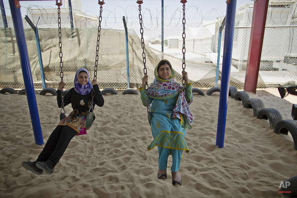 "Nobel Peace Prize recipient Malala Yousafzai, 18, right, and Mezon al-Melihan, a 17-year-old refugee from the southern Syrian town of Deraa, enjoy a swing ride during Malala's visit to Azraq refugee camp in Jordan, Monday, July 13, 2015. Rich countries should spend less on weapons in the Syria conflict and more on education, Malala said Monday, calling world leaders ""quite stingy"" as she visited a camp for Syrian war refugees. (AP Photo/Muhammed Muheisen)"
