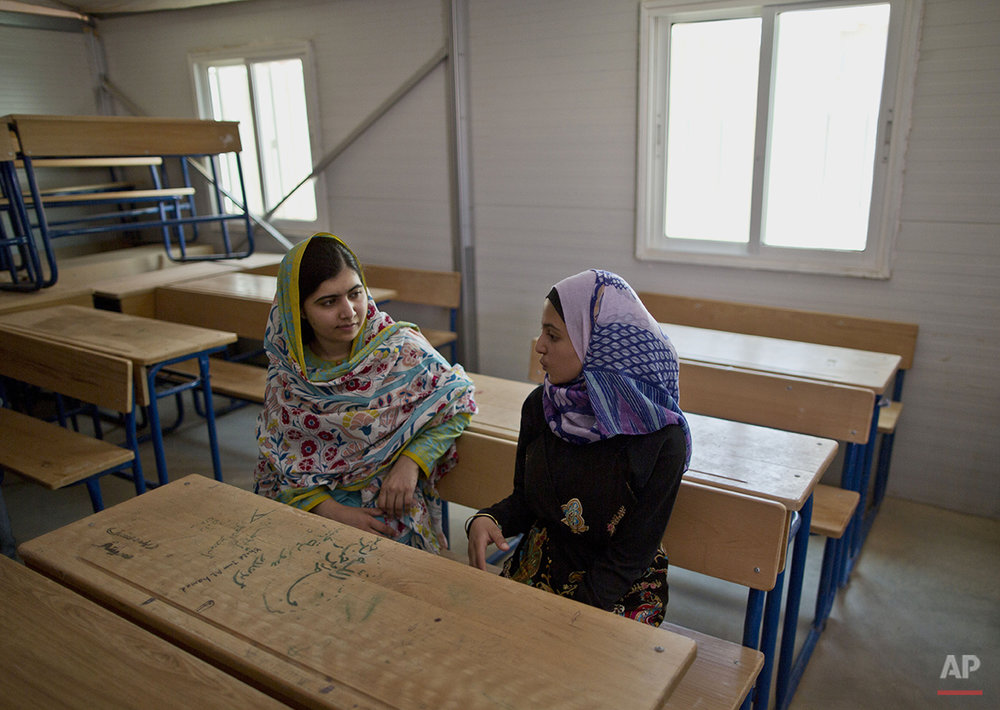 "Nobel Peace Prize laureate Malala Yousafzai, 18, left, and Mezon al-Melihan, a 17-year-old refugee from the southern Syrian town of Deraa, talk while visiting a class at Azraq refugee camp, Jordan, Monday, July 13, 2015. Rich countries should spend less on weapons in the Syria conflict and more on education, Nobel Peace Prize winner Malala Yousafzai said Monday, calling world leaders ""quite stingy"" as she visited the camp for Syrian war refugees. (AP Photo/Muhammed Muheisen)"