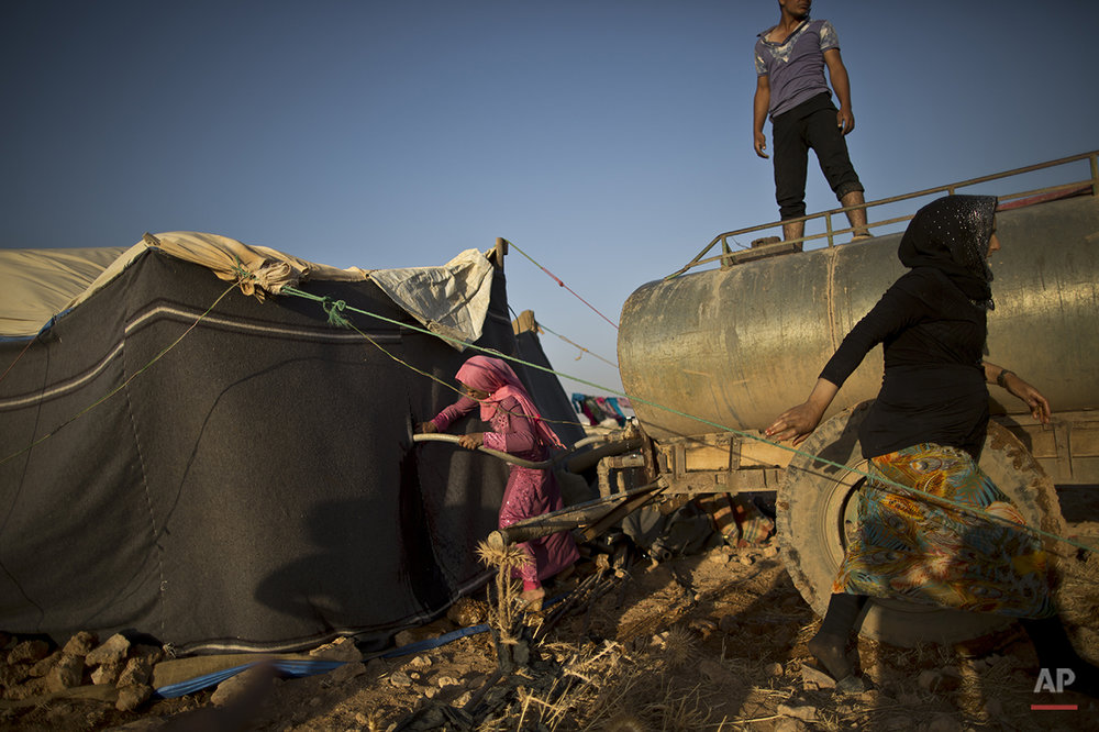 In this Saturday, July 25, 2015 photo, a Syrian refugee girl fills water from a tanker to her tent at an informal tented settlement near the Syrian border on the outskirts of Mafraq, Jordan. Aid agencies asked for $4.5 billion for 2015 to help refugees, but have been forced to slash support programs because of large funding gaps. That's had a devastating effect on the amount of food aid coming. (AP Photo/Muhammed Muheisen)