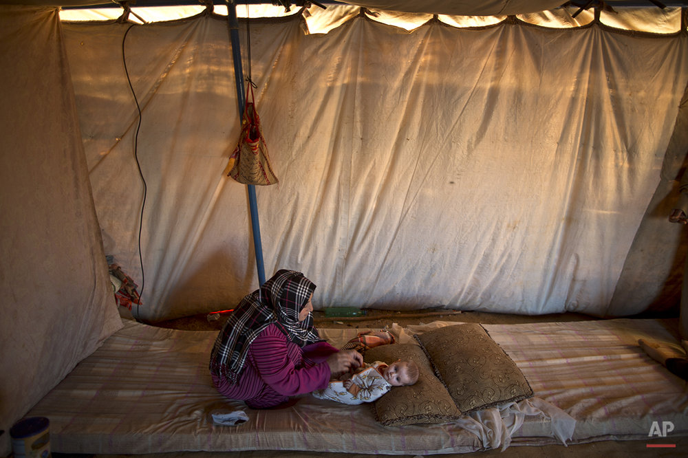 "In this Tuesday, July 21, 2015 photo, Syrian refugee Naela Mohammed, 31, changes the clothes of her daughter Asmahan, 4 months, at their tent in an informal tented settlement near the Syrian border on the outskirts of Mafraq, Jordan. Naela worries about being able to nurse her child while she herself doesn't have enough to eat. ""It's a sure thing my 4-month daughter will be paying the price,"" Mohammed says. ""She's so tiny and weak.""  (AP Photo/Muhammed Muheisen)"