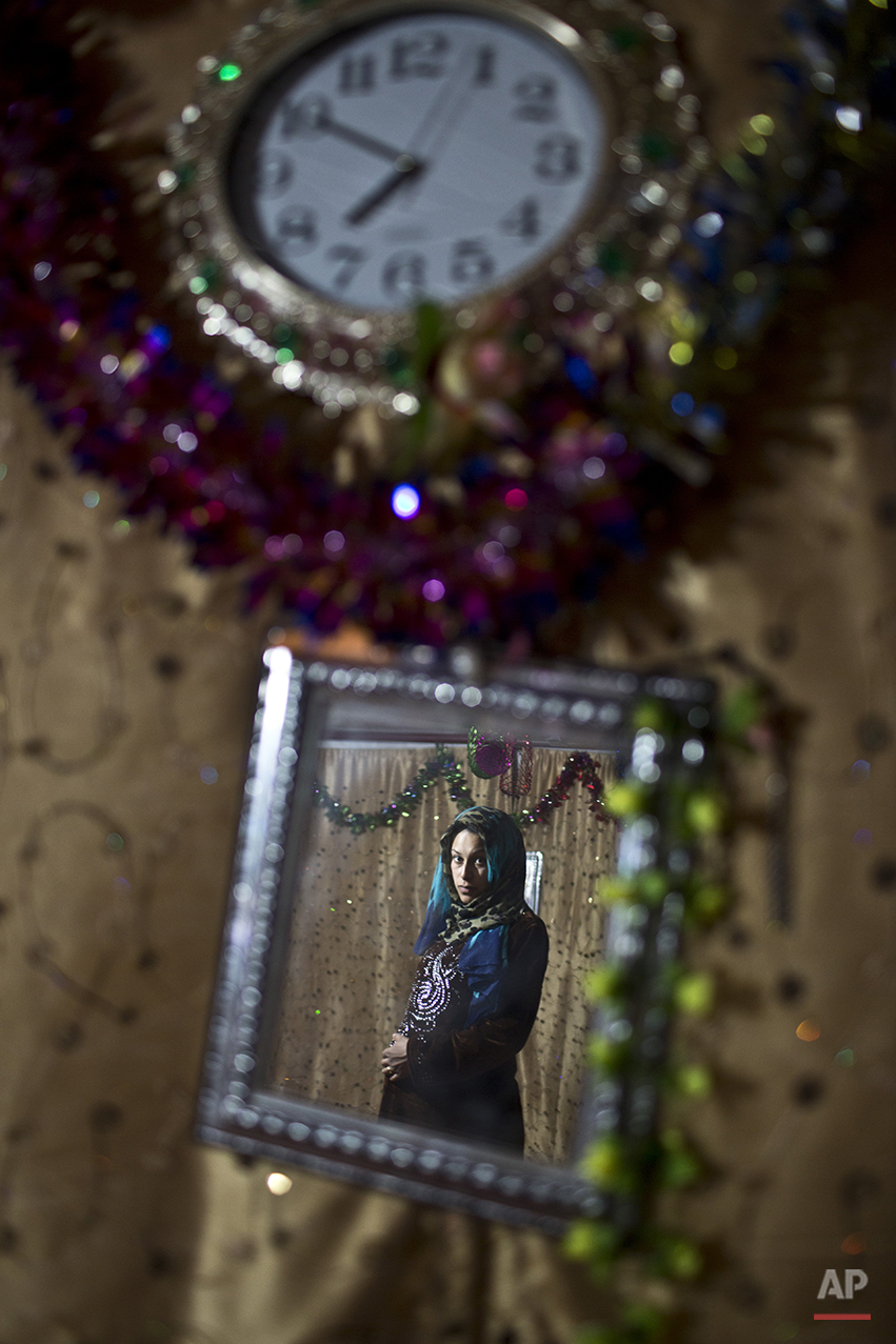 In this Saturday, July 25, 2015 photo, pregnant Syrian refugee Huda Alsayil, 20, who passed her 9th month of pregnancy, is reflected in a mirror while posing for a portrait inside her tent at an informal tented settlement near the Syrian border on the outskirts of Mafraq, Jordan. More than 10,000 children have died in Syria's four-year conflict, while over 2.8 million in and out of the country don't go to school, according to the U.N. children's agency, UNICEF. (AP Photo/Muhammed Muheisen)