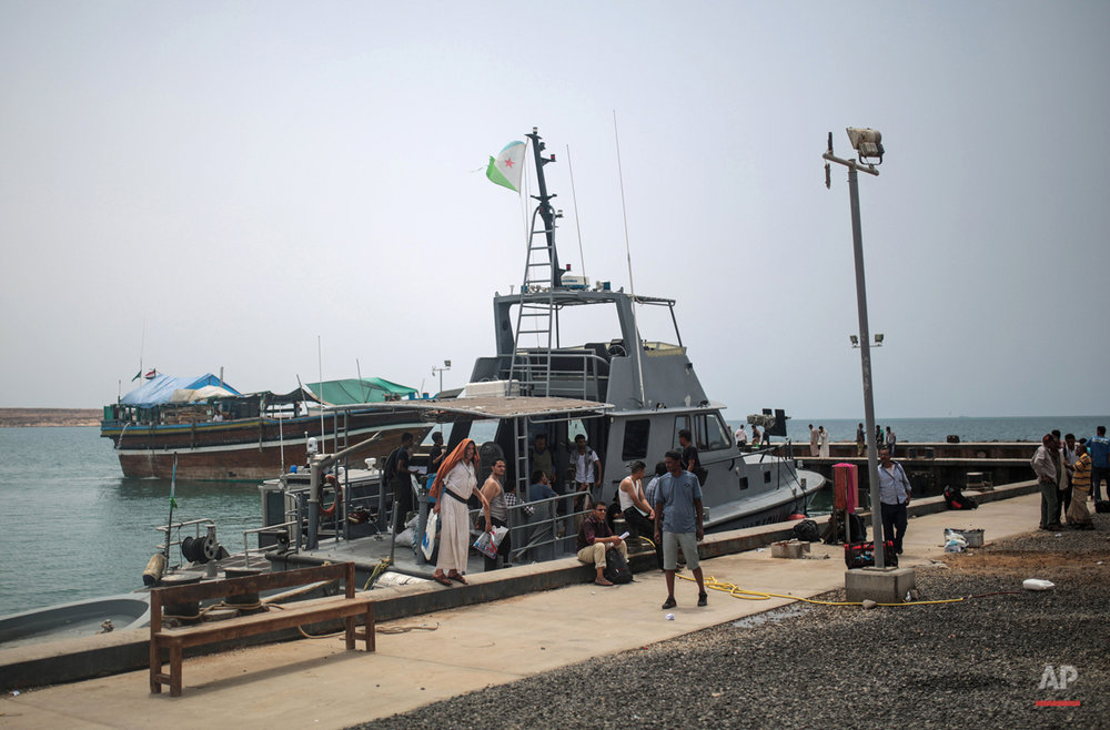 In this Tuesday, May 19, 2015 photo, newly-arrived Yemeni refugees wait at the Obock port in northern Djibouti. Many of the refugees arrived with just the few belongings they could carry, mostly on small rickety fishing boats, others on bigger vessels crammed with people, reversing a centuries-old perilous route that has seen countless African migrants take to the seas in the other direction. (AP Photo/Mosa'ab Elshamy)
