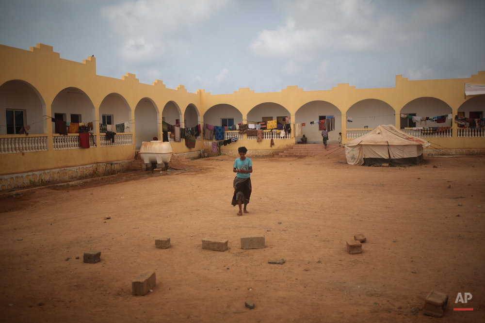 In this Wednesday, May 20, 2015 photo, a Yemeni refugee walks at the yard of an orphanage that has been turned into a center for Yemeni refugees, in Obock, northern Djibouti. The Al-Rahma orphanage has become home to about 100 families, mostly from the Yemeni town of Bab Al-Mandab just a 30-minute boat trip from Obock. (AP Photo/Mosa'ab Elshamy)
