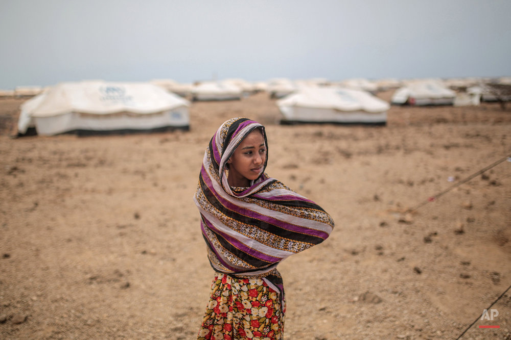 In this Tuesday, May 19, 2015 photo, Ashwaq, 12, stands outside her family's tent, at the Markaze refugee camp in Obock, northern Djibouti. Fleeing the war at home, thousands of Yemenis have made it across the Gulf of Aden to find refuge in Djibouti, a sleepy Horn of Africa nation where the United Nations has set up a staging hub for aid for the conflict-torn Arab country. (AP Photo/Mosa'ab Elshamy)