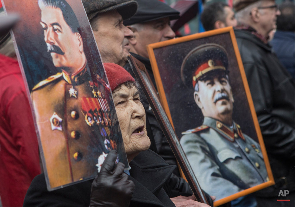 Communists carry portraits of former Soviet leader Josef Stalin as they march along Kremlin Towers during May Day demonstration in Moscow, Friday, May 1, 2015. As in Soviet times, tens of thousands of cheerful workers paraded across Red Square despite a chilly rain, but instead of red flags with the Communist hammer and sickle, they waved the blue flags of the dominant Kremlin party and the Russian tricolor. Participants, who came in groups organized by their trade unions, said the May 1 parade was a tradition going back to their childhood. (AP Photo/Denis Tyrin)