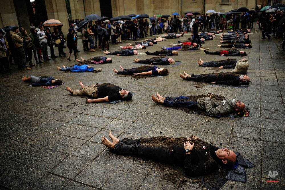 Relatives of people killed in the Spanish Civil War (1936-1939) lay on the street after having their bodies covered with earth by artist Abel Axcona as a tribute to people killed in the war during a performance, in Pamplona northern Spain, Friday May 1, 2015. (AP Photo/Alvaro Barrientos)