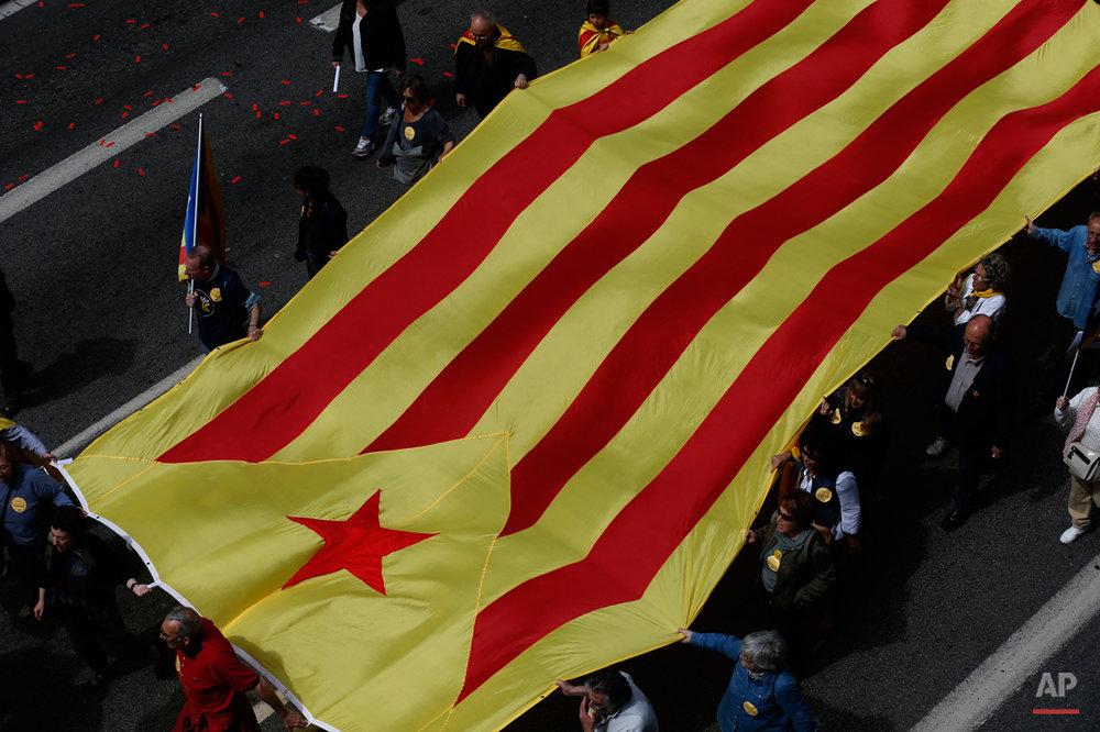 People wave an estelada flag (pro-independence Catalan flag) as they protest during a May Day rally in the center of Barcelona, Spain, Friday, May 1, 2015. May 1 is celebrated as International Labor Day or May Day across the world. (AP Photo/Manu Fernandez)