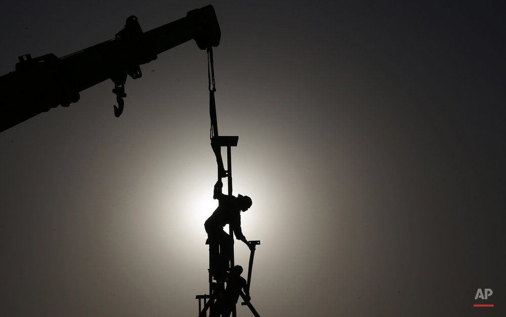 Indian laborers are seen silhouetted as they dismantle a temporary structure in Hyderabad, India, Friday, May 1, 2015. May 1 is marked as the International Labor Day or May Day across the world. (AP Photo/Mahesh Kumar A.)